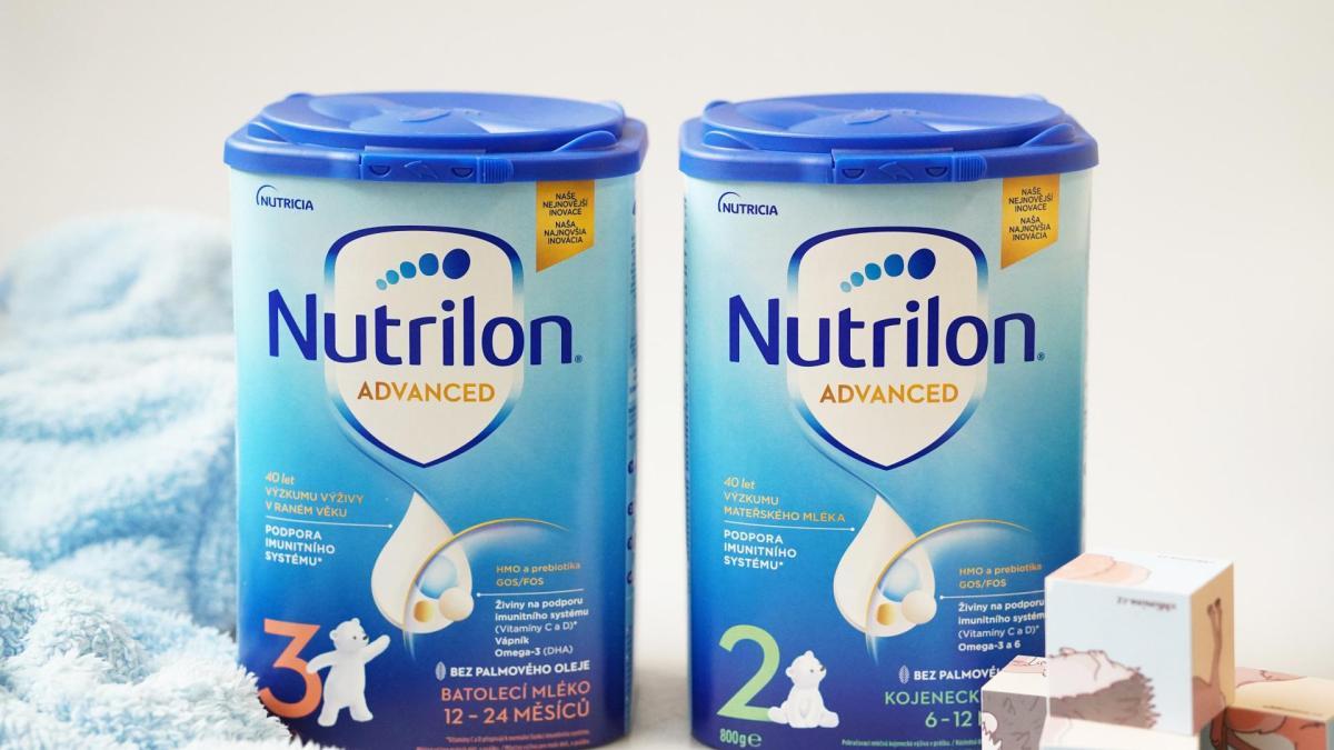 Pokračovací a batolecí výživa Nutrilon Advanced 2 a3 v zátiší s dětskými dřevěnými kostkami a modrým ručníkem