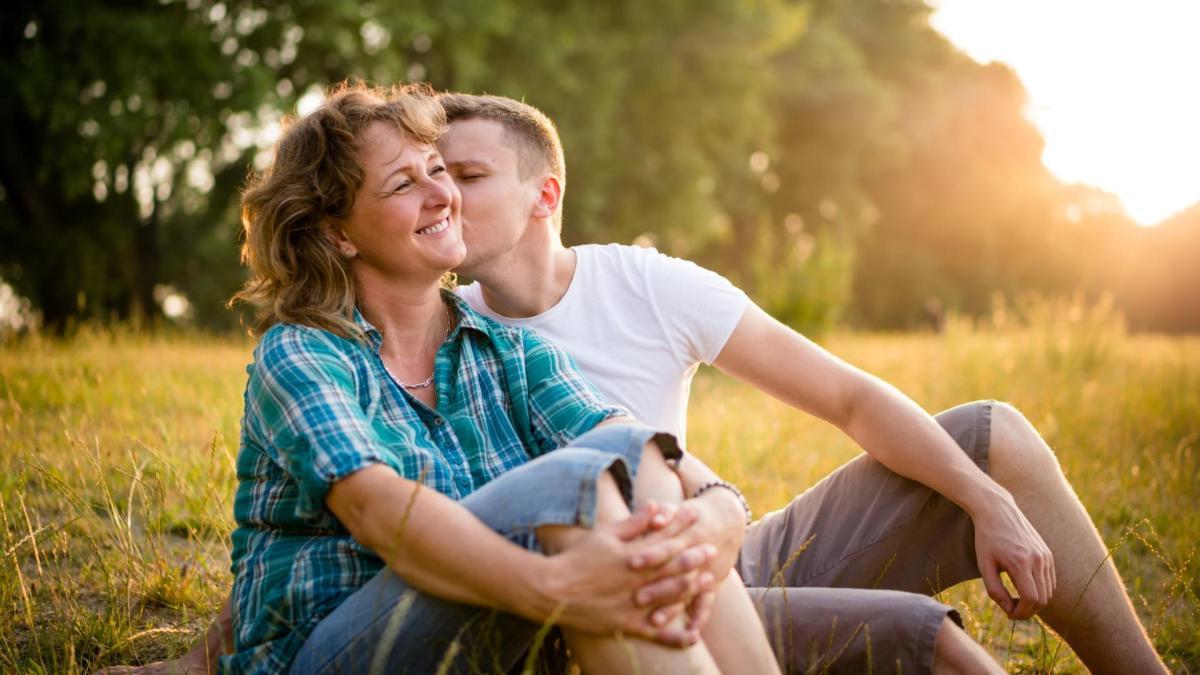 Mladší partner líbá svoji spokojenou partnerku na tvář