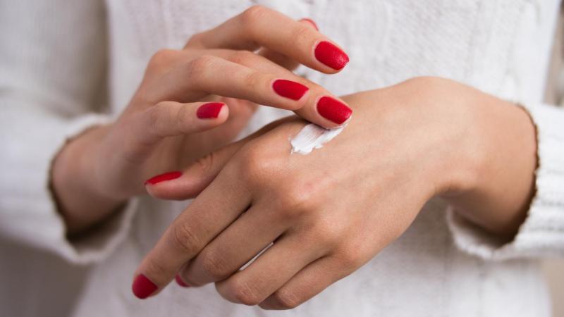 Detail rukou, žena si nanáší krém na ruce