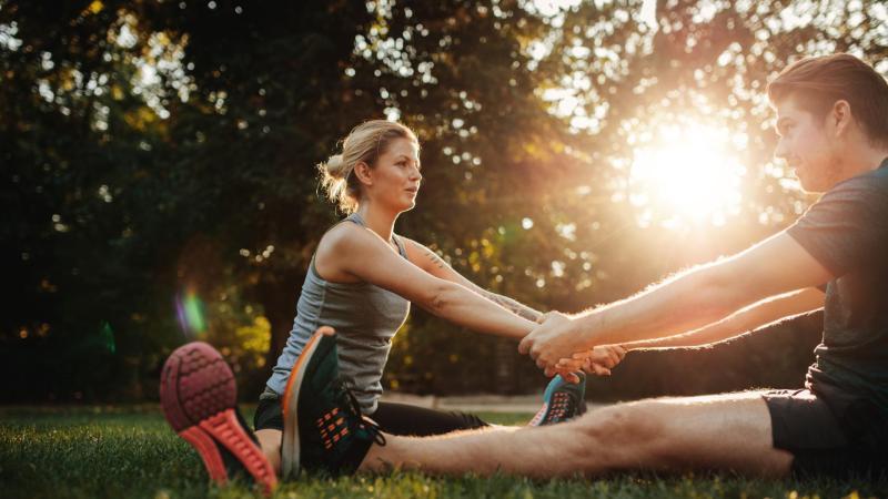 Muž a žena společně cvičí v parku při západu slunce.