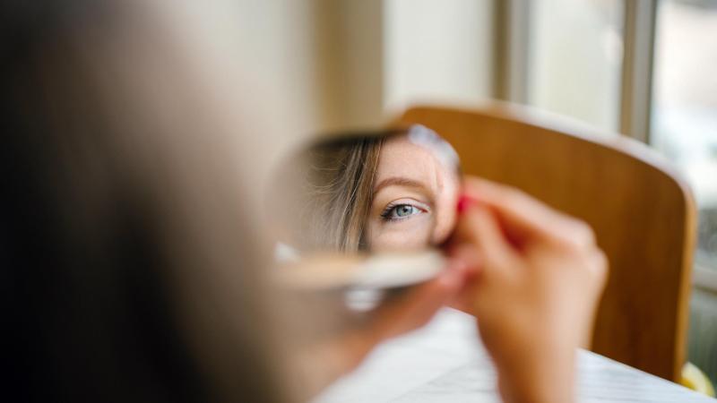 Žena kouká do zrcátka. Záběr na oko.
