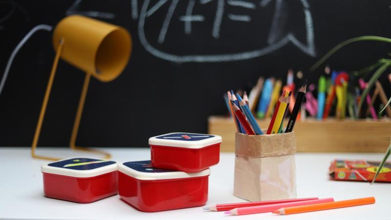 Svačinové boxy a pastelky na psacím stole školáka