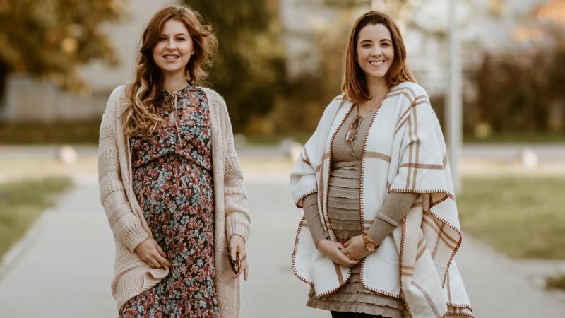 Dvě těhotné kamarádky ve volných šatech a ponču v posledním stadiu těhotenství, těhotenské bříško