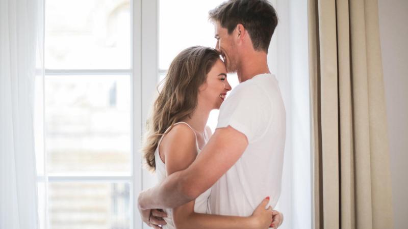 Muž a žena se objímají v obývacím pokoji u okna.