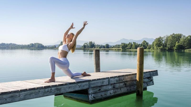 Žena v jógové pozici Mírumilovného bojovníka, lázně u jezera Tachinger See. Ideální příležitost pro