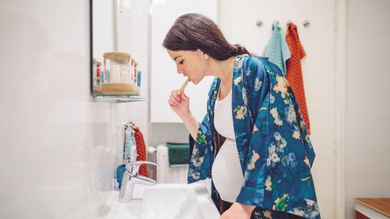 Těhotná žena si pečlivě čistí zuby, péče o zuby v těhotenství.