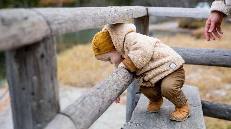 Malé dítě si hraje na dřevěné lavičce oblečené v teplé bundě a mikině
