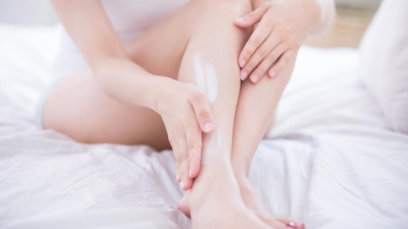 Žena nanáší krém na nohy