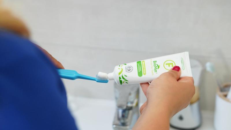 Žena si na kartáček TePe nanáší zubní pastu s fluoridem, čištění zubů v těhotenství.