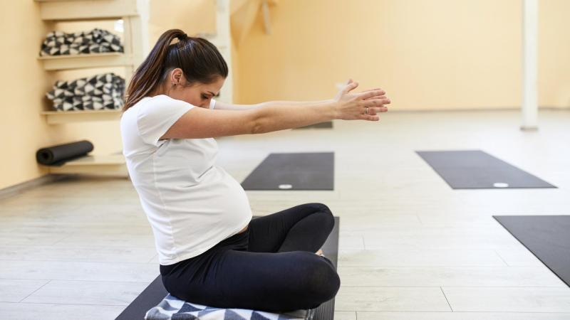 Těhotná žena se protahuje na jógamatce, strie v těhotenství.