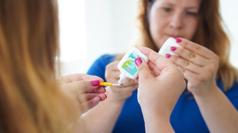 Žena nanáší na mezizubní kartáček gel s obsahem fluoridu, čištění zubů v těhotenství.